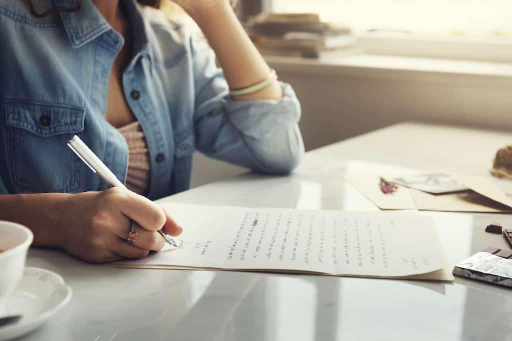 A woman writing a wedding anniversary card