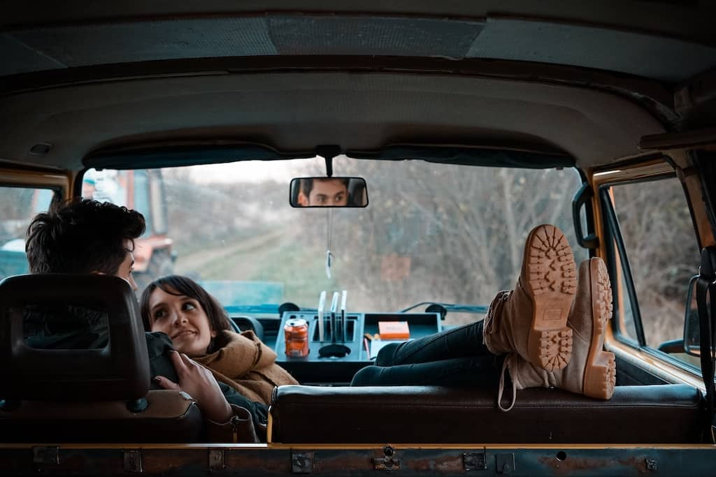 a man and woman resting during a road trip on anniversary
