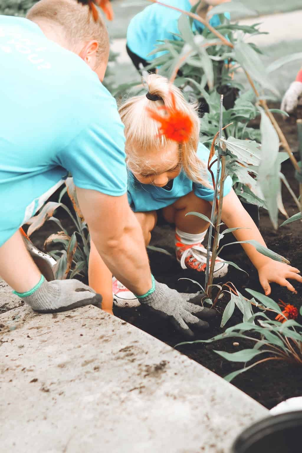 ideas for anniversary - volunteering - a man helping a little girl to plant a tree