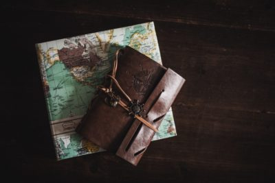 a leather journal notebook lying on a map