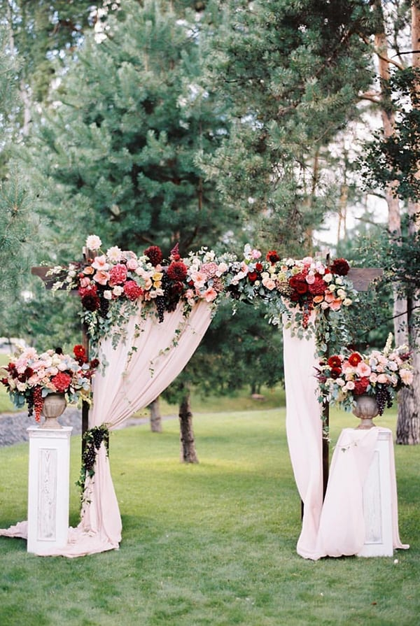 floral ceremony arch draped with white cloth
