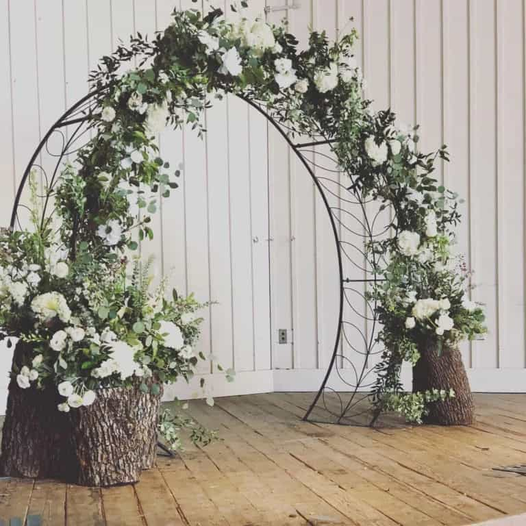 circle wedding arbor decorated with greens & flowers