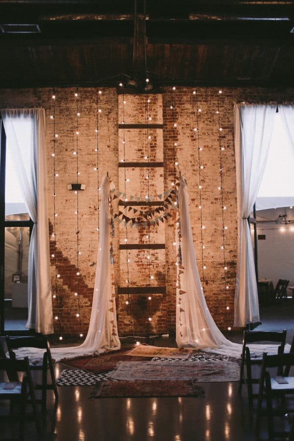 wedding backdrop ideas: whimsical backdrop decorated with fabric & light strings