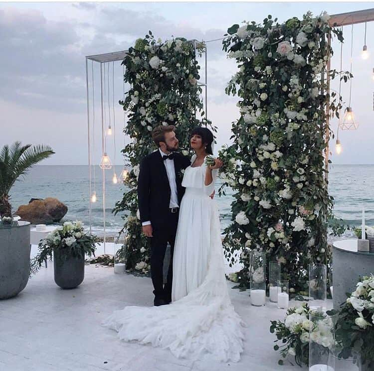 wedding photo backdrop idea decorated with greenery and light strings