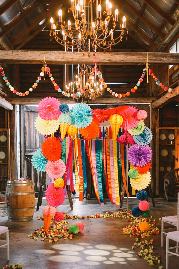 wedding photography backdrop decorated with colorful pom poms and ribbons