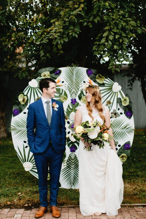 outdoor wedding backdrop idea: round backdrop decorated with tropical leaves