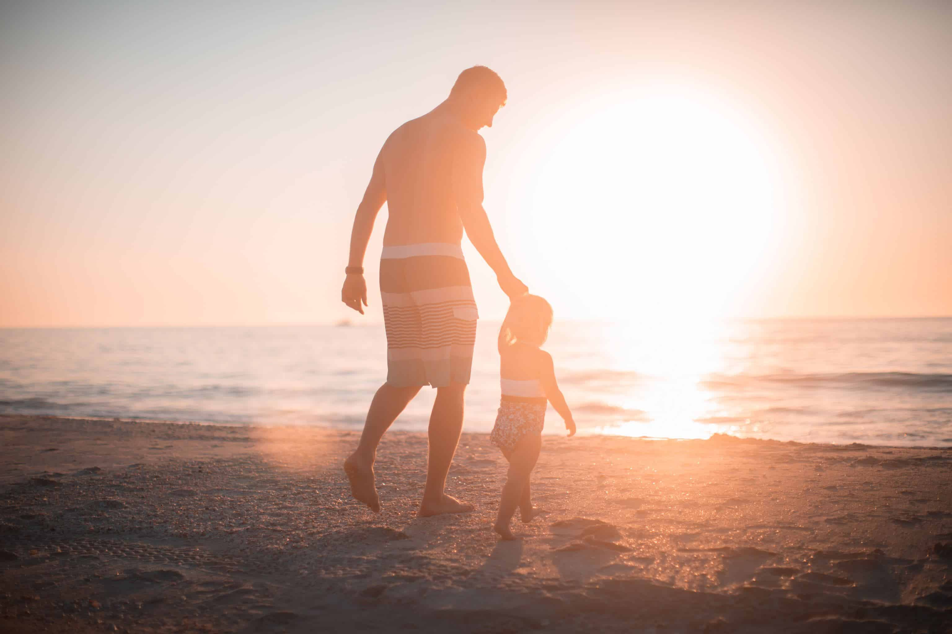 fathers day messages thumbnal: man holding child's hand walking on a beach