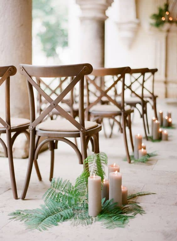 wedding aisle decorated with ferns and candles as markers