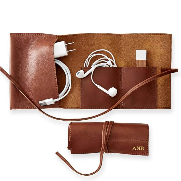 A leather roll up containing cords, chargers and headphones