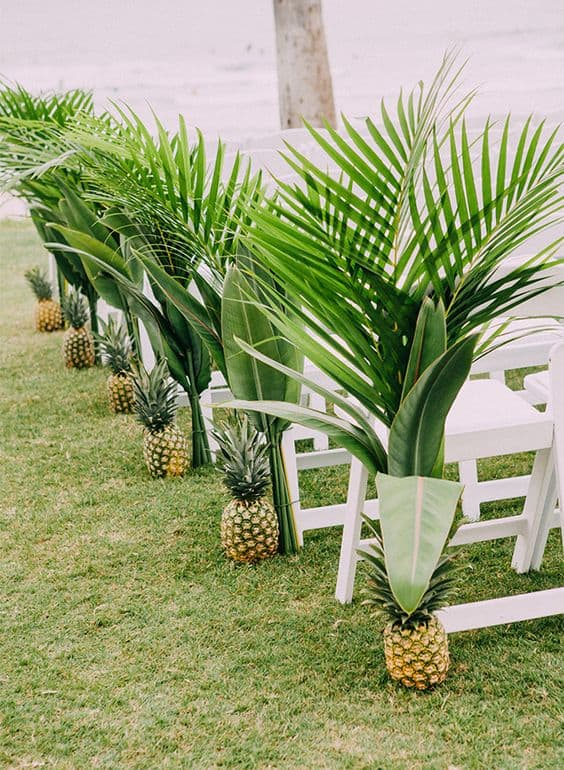 tropical wedding aisle marker ideas with leaves and pineapples