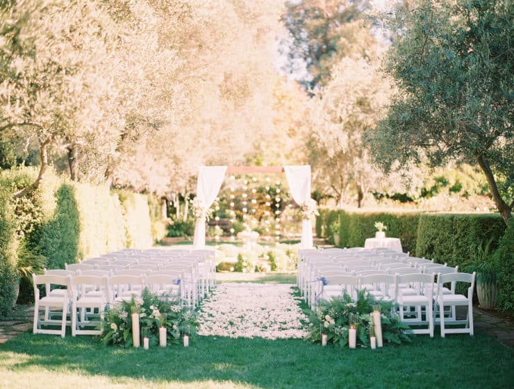 outdoor wedding aisle decor idea with flower petals, greenery and candles