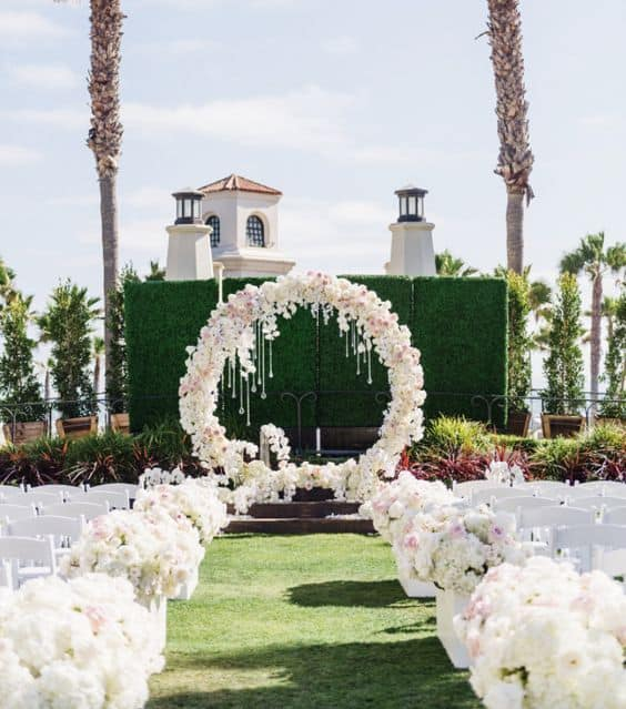 white floral aisle markers and circular ceremony arch