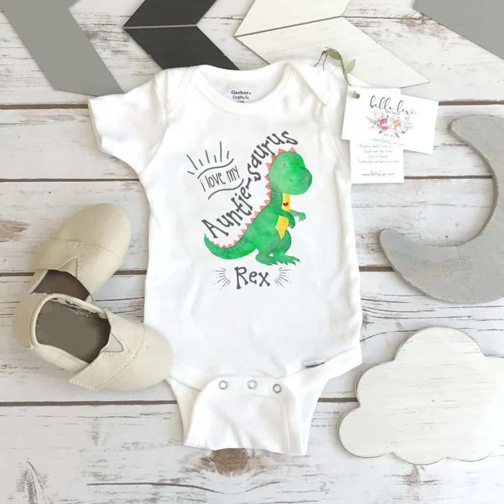 White Aunt Baby Bodysuit with the picture of a dinosaur.