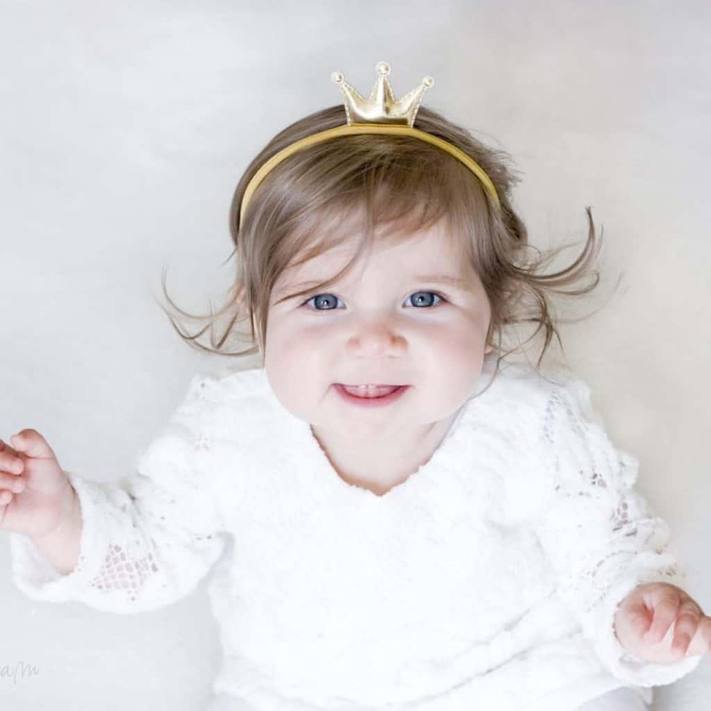 A baby girl wearing a Princess Gold Headband