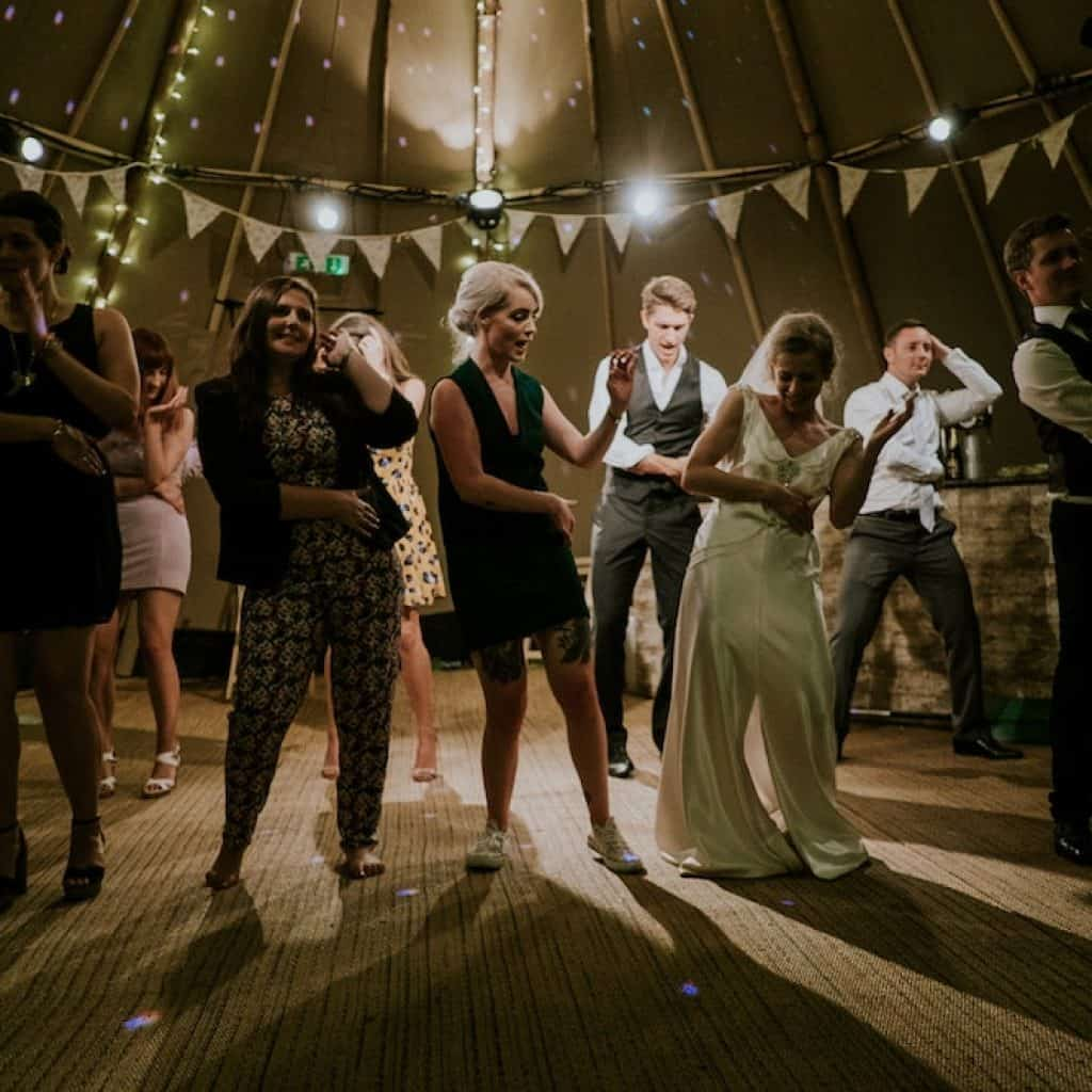 bride groom and guests dancing at reception
