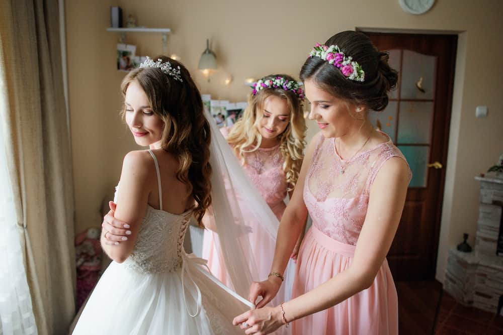 Bridesmaids help bride to get ready for a wedding