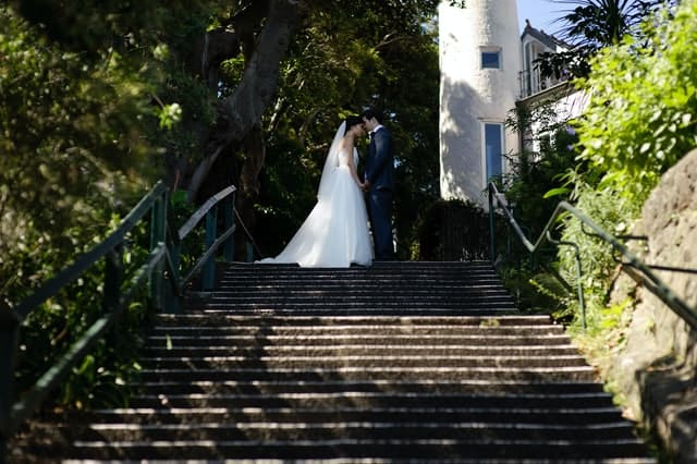 bride and groom standing in front of each other on stairs